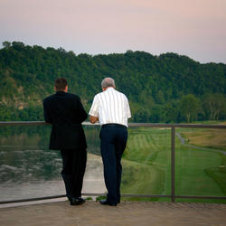 son and father on patio overlooking pete dye river course