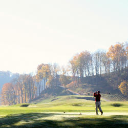 man teeing off at pete dye river course
