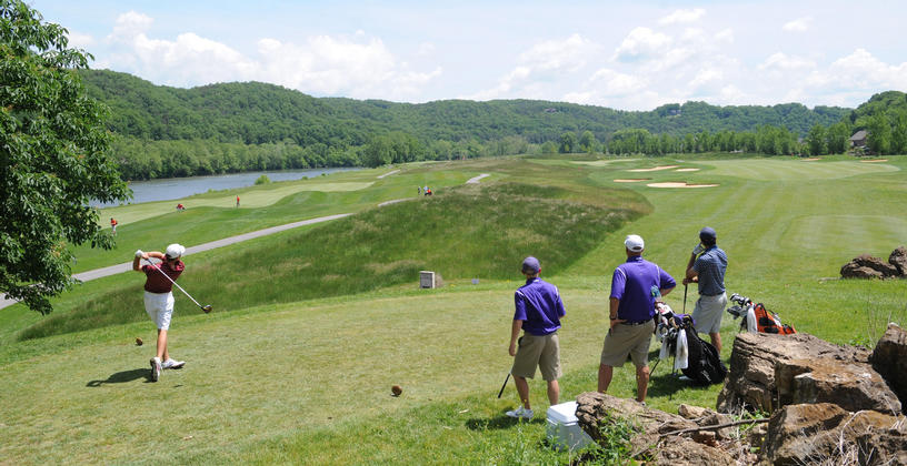man teeing off at pete dye river course with three men looking on