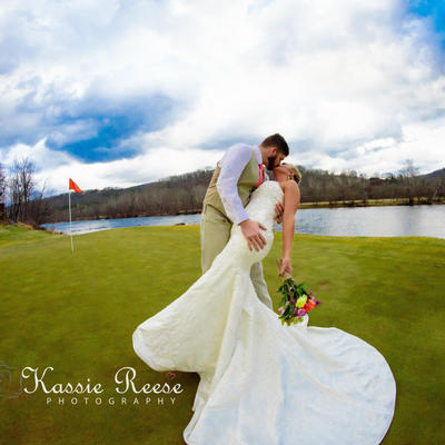 bride and groom kissing on pete dye river course