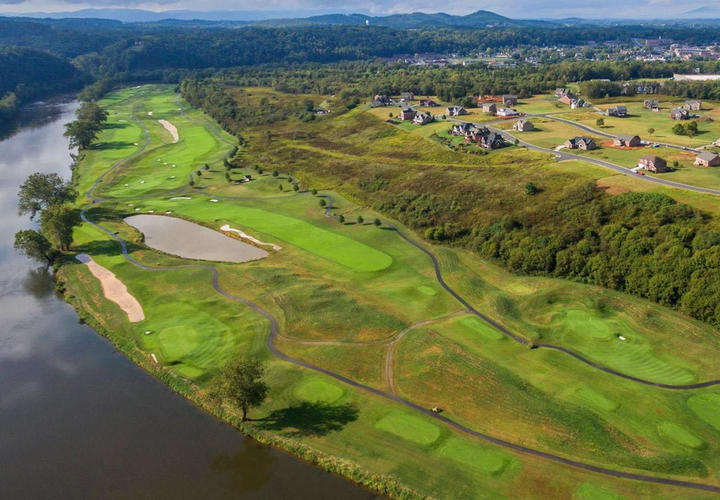 aerial view of pete dye river course next to neighborhood of houses