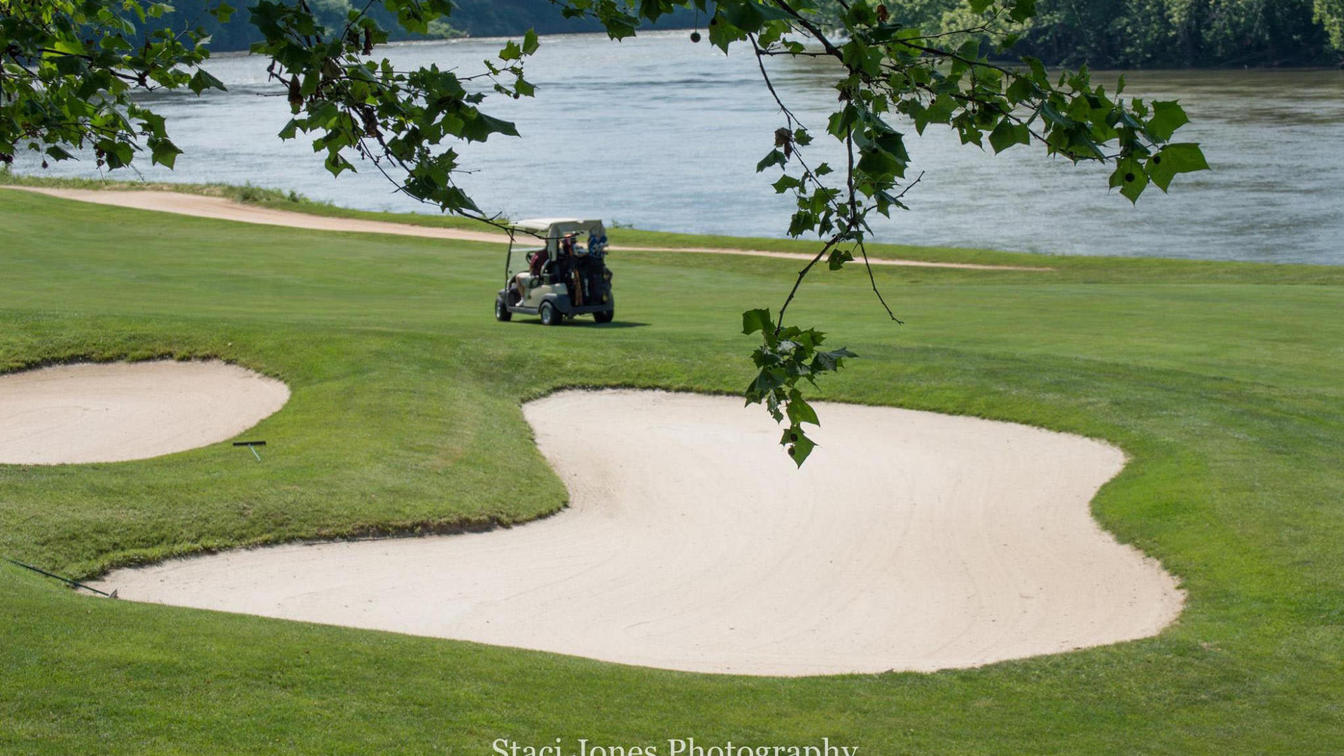 two men driving golf cart on pete dye river course