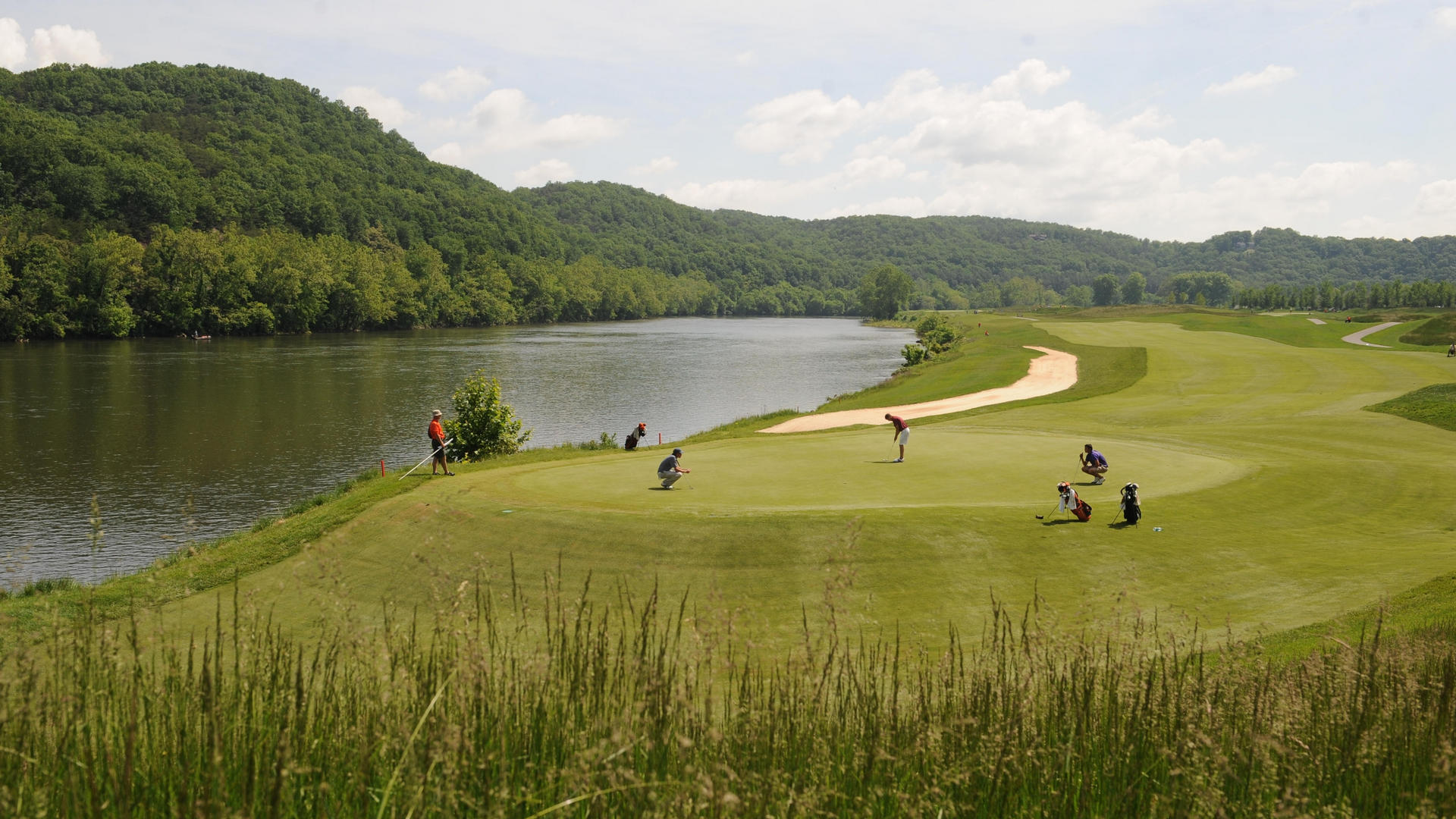 man putting on green at pete dye river golf course